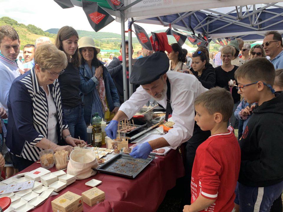 Cocinero en la Fiesta de la Sal en Salinas de Oro ofreciendo aperitivos de Cordero de Navarra a los asistentes al evento